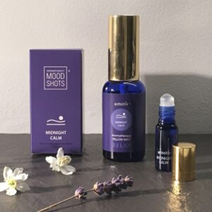 Deep relaxation aromatherapy blends for sleep. Photo shows MIDNIGHT CALM roll on aromatherapy blend and Lavender Pillow Spray in blue glass bottles with gold lids